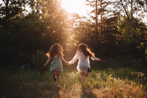 Back view of girlfriends holding hands while running in summer forest - CAVF89835