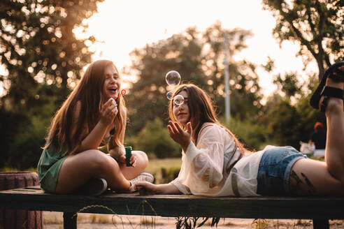 Happy lesbian couple playing with bubbles relaxing in park in summer - CAVF89841