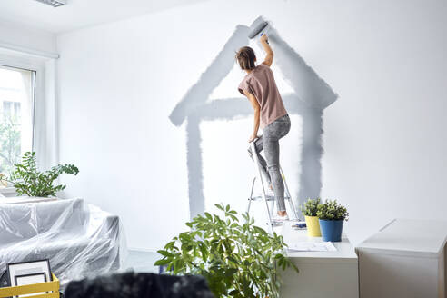 Young woman making house with paint roller on wall while standing on ladder at home - BSZF01725