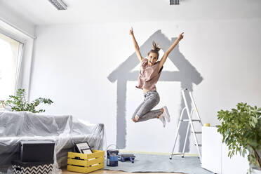 Carefree woman with hand raised jumping against wall at home - BSZF01743