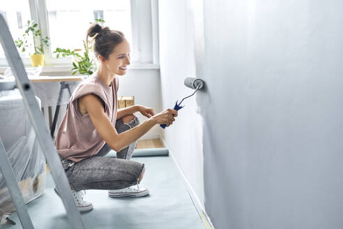 Young woman painting wall with paint roller while crouching at home - BSZF01746