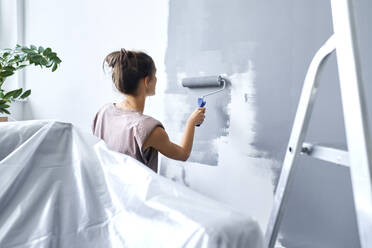 Young woman using paint roller while painting wall at home - BSZF01749