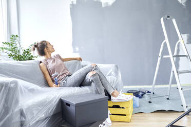 Woman with paint roller looking at wall while sitting on sofa at home - BSZF01752