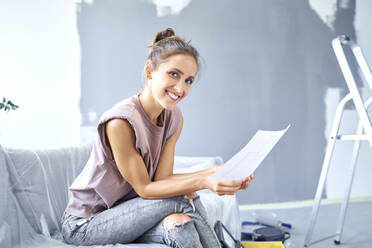 Smiling woman reading paper while sitting on sofa at home - BSZF01755