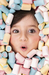 Girl face surrounded with marshmallow looking surprised - GEMF04277