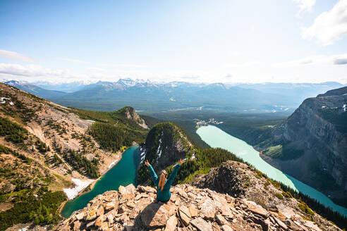 Hiker Celebrating Above Lake Louise and Lake Agnes on Devil's Thumb - CAVF89941