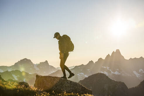 Back lit backpacker standing on mountain summit with scenic view - CAVF89986