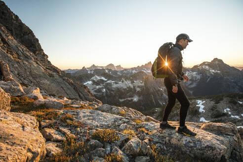 Backpacker hikes across rocky terrain on mountain pass. - CAVF89992