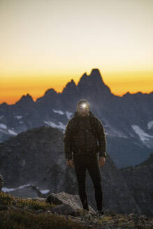 Backpacker hikes with headlamp on at dusk. - CAVF89995