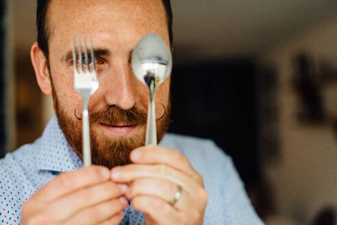 Close up portraits of man with moustache holding fork and spoon - CAVF90004