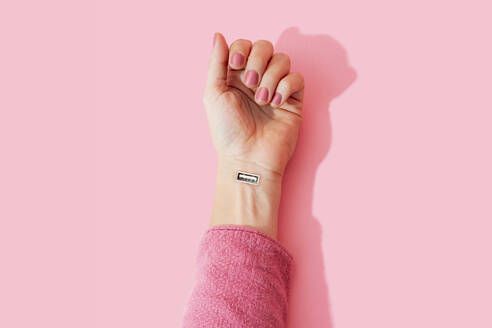 Cropped image of woman hand with USB port against pink wall - GEMF04280