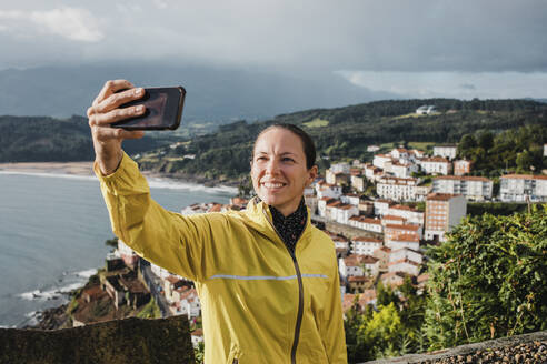 Smiling woman taking selfie with village through mobile phone during vacations - DMGF00204