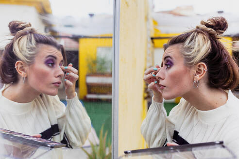 Young woman applying eye shadow looking at mirror while standing in back yard - MRRF00583