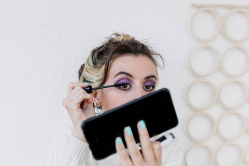 Woman applying mascara looking in smart phone while standing against white wall - MRRF00589
