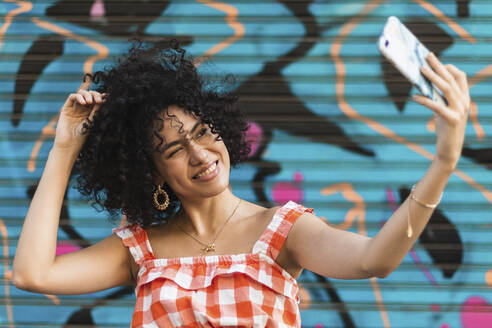 Young woman taking selfie on smart phone standing against art wall - PNAF00020