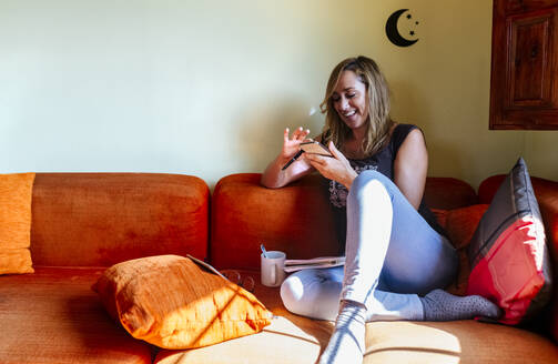 Happy woman at home sitting on sofa text messaging using mobile phone - MGOF04608