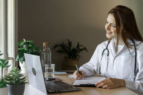 Young female doctor writing medical report during online consultation from home office - AFVF07375