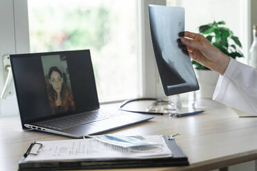 Young female doctor examining x-ray during online consultation from home office - AFVF07384