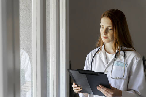 Young female doctor examining medical record at home office - AFVF07390