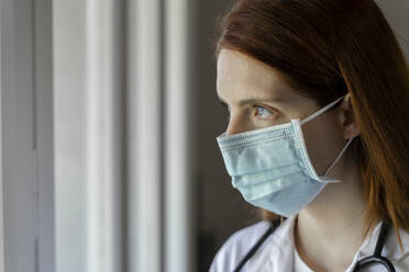 Thoughtful young female doctor wearing face mask during COVID-19 - AFVF07393