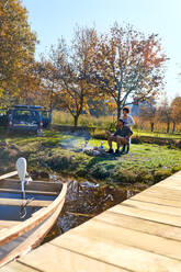 Young couple camping at sunny autumn lakeside - CAIF29826