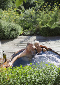 Portrait happy senior couple relaxing in hot tub on sunny patio - CAIF29850