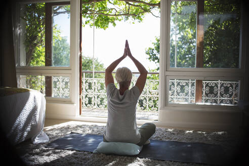 Serene senior woman practicing yoga at sunny tranquil balcony doorway - CAIF29913
