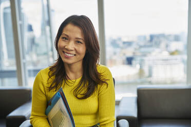Portrait smiling businesswoman with paperwork in office - CAIF29955
