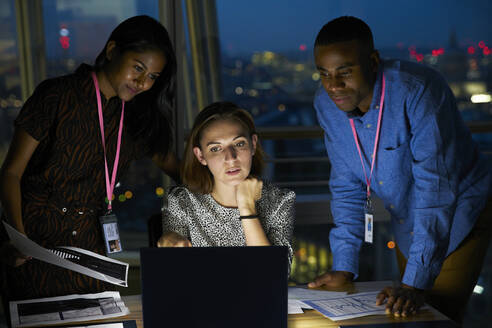 Business people working late at laptop in office - CAIF29961