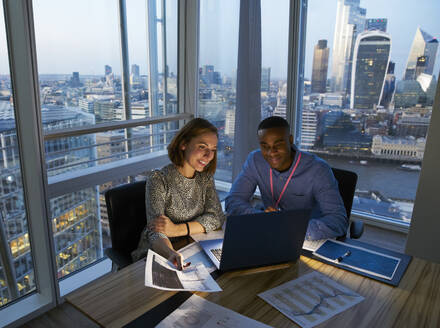 Business people working at laptop in highrise office, London, UK - CAIF29970