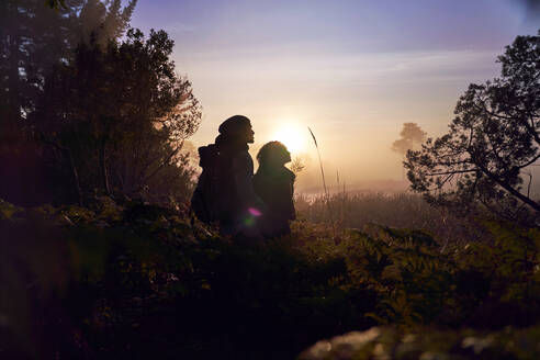 Silhouette serene young couple enjoying hike in nature at sunset - CAIF30009
