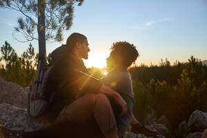 Affectionate young hiking couple enjoying tranquil sunset in woods - CAIF30066