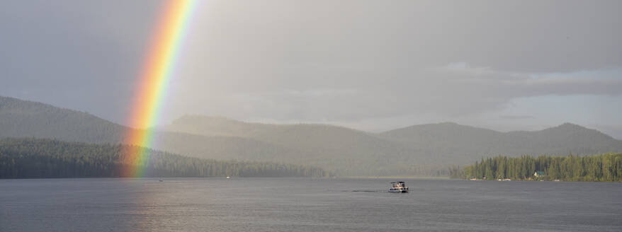 Vivid rainbow shining over calm lake with pontoon boat in countryside - CAVF90166