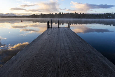 Wooden pier with ladder by lake during sunset and reflection of clouds - CAVF90169