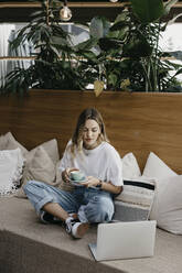 Young woman holding coffee cup while using laptop sitting on sofa - LHPF01314