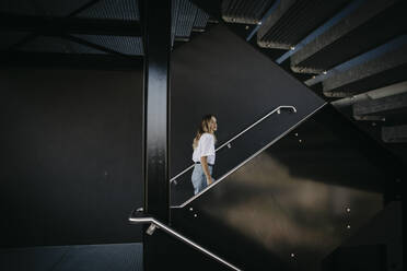 Young woman climbing on steps - LHPF01335