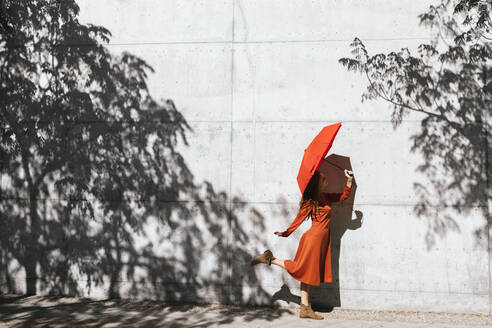 Woman in red dress holding red umbrella while standing against tree shadow wall - TCEF01219