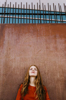 Redheaded beautiful woman leaning against a wall outdoors - TCEF01254