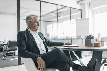 Businessman looking away while sitting on chair at office - GUSF04475