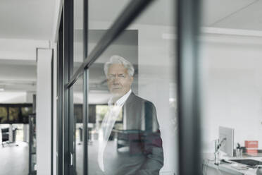 Businessman looking away while standing by glass wall at office - GUSF04478