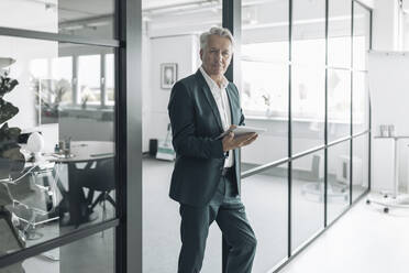 Businessman using digital tablet while leaning on wall at office - GUSF04481