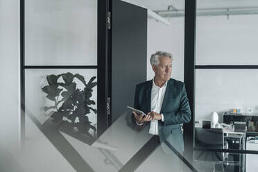 Businessman wearing suit using digital tablet while standing at office - GUSF04520