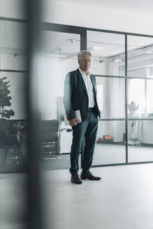 Man wearing suit holding digital tablet while standing at office - GUSF04526