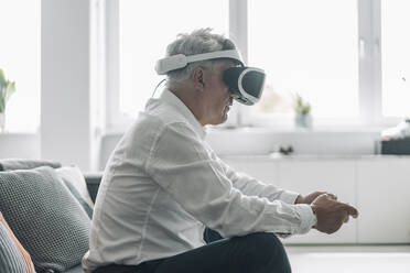 Businessman playing video game with virtual reality eyeglasses while sitting on sofa at office - GUSF04547