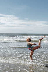 Girl doing gymnastics while standing in water at beach on sunny day - OGF00596