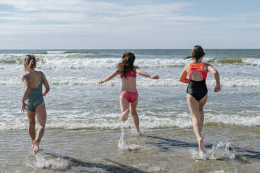 Friends running in water at beach on sunny day - OGF00599
