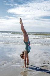 Girl gymnast doing upside on sand at beach during sunny day - OGF00602