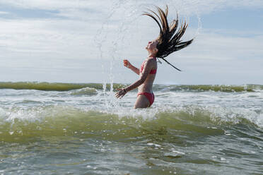 Girl with tousled hair standing in water at beach on sunny day - OGF00605