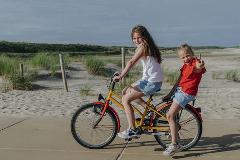 Girl taking younger sibling on bicycle at beach during sunny day - OGF00608