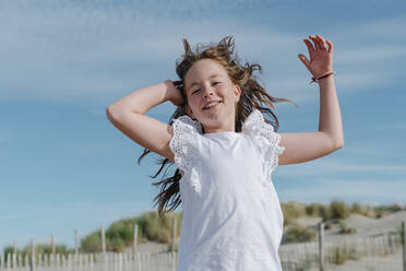 Girl with hand in hair standing at beach on sunny day - OGF00611
